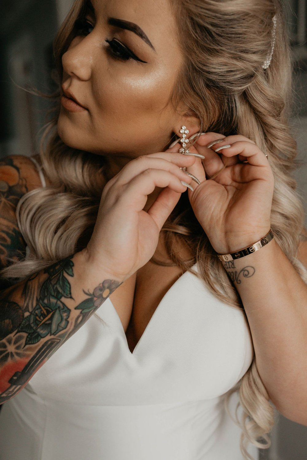 Bride putting on her ear rings by anthropologie - Matt Smarsh and Johanna Dye - suites by the black tux - Raleigh North Carolina Urban Edgy Downtown Wedding - suits by the black tux