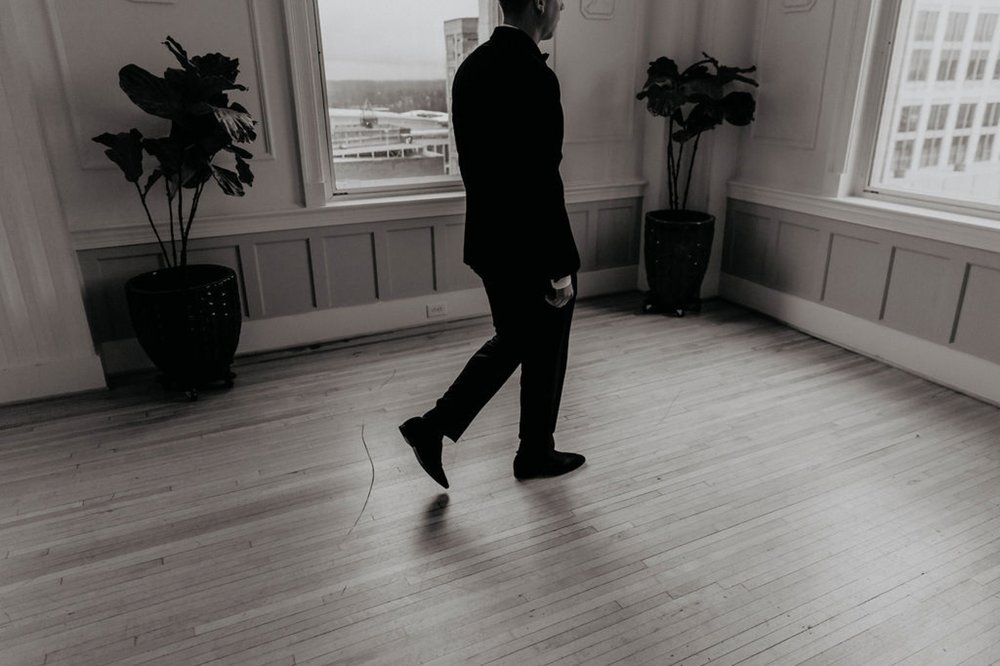Groom walking into the cannon room - Matt Smarsh and Johanna Dye - suites by the black tux - Raleigh North Carolina Urban Edgy Downtown Wedding - suits by the black tux