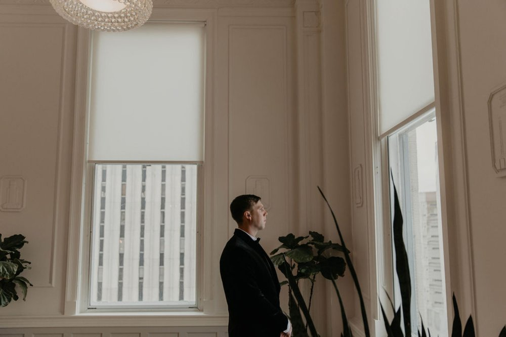 Groom looking out of the window of the cannon room - Matt Smarsh and Johanna Dye - suites by the black tux - Raleigh North Carolina Urban Edgy Downtown Wedding - suits by the black tux