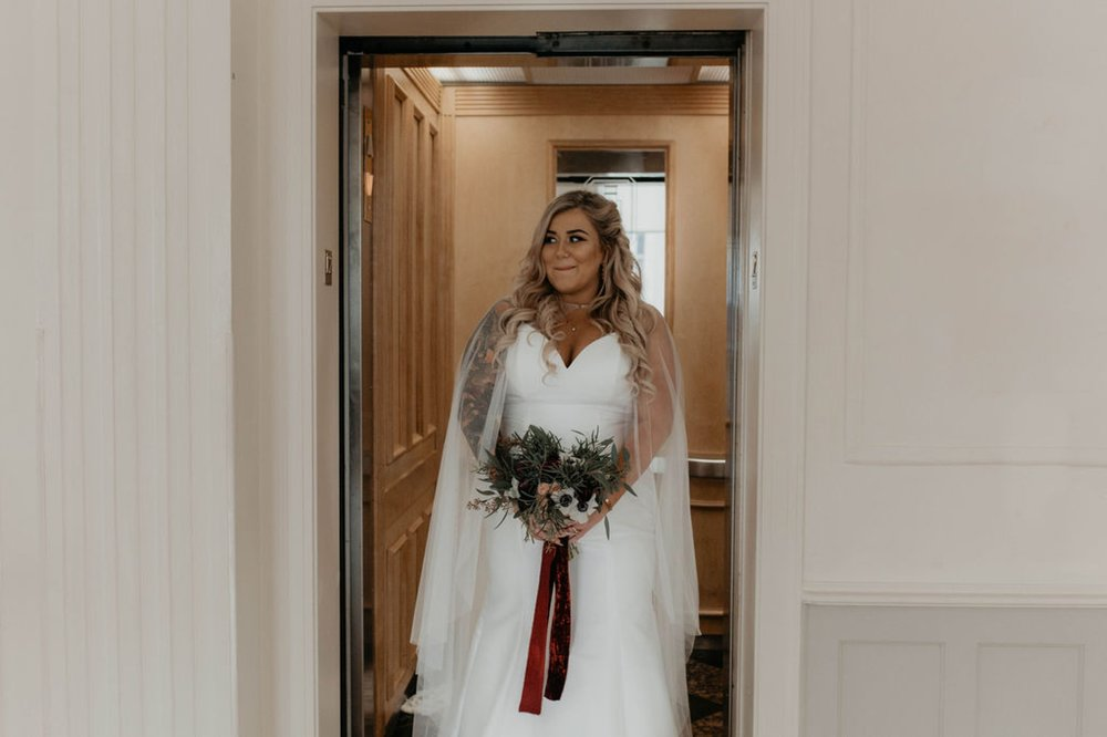 Bride arriving in the elevator of the cannon room excited for the first look with her groom - Bride in an Allure Bridals Mermaid Gown - Matt Smarsh and Johanna Dye - suites by the black tux - Raleigh North Carolina Urban Edgy Downtown Wedding - suits by the black tux