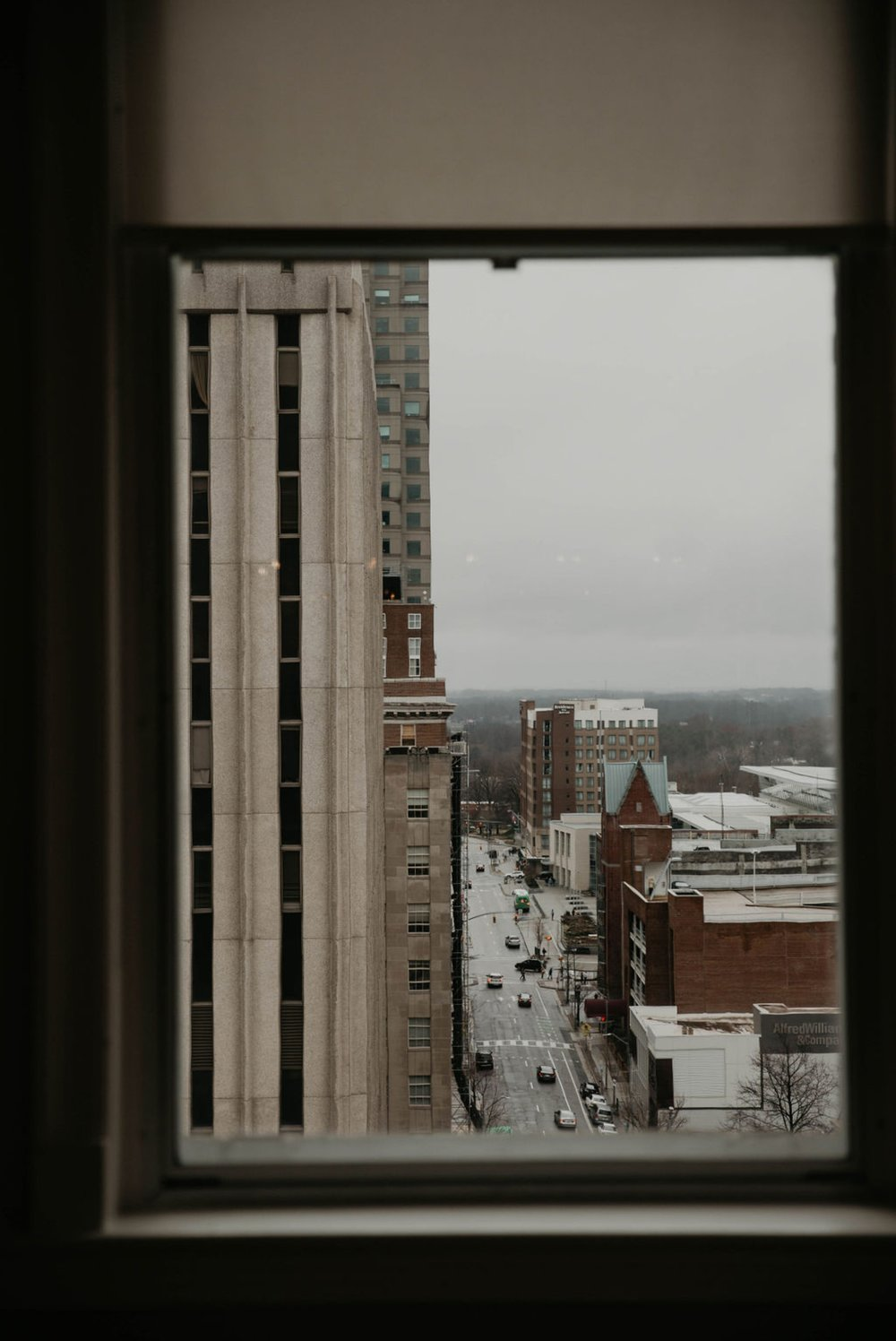 Looking out the window of the cannon room - - Bride in an Allure Bridals Mermaid Gown - Matt Smarsh and Johanna Dye - suites by the black tux - Raleigh North Carolina Urban Edgy Downtown Wedding - suits by the black tux