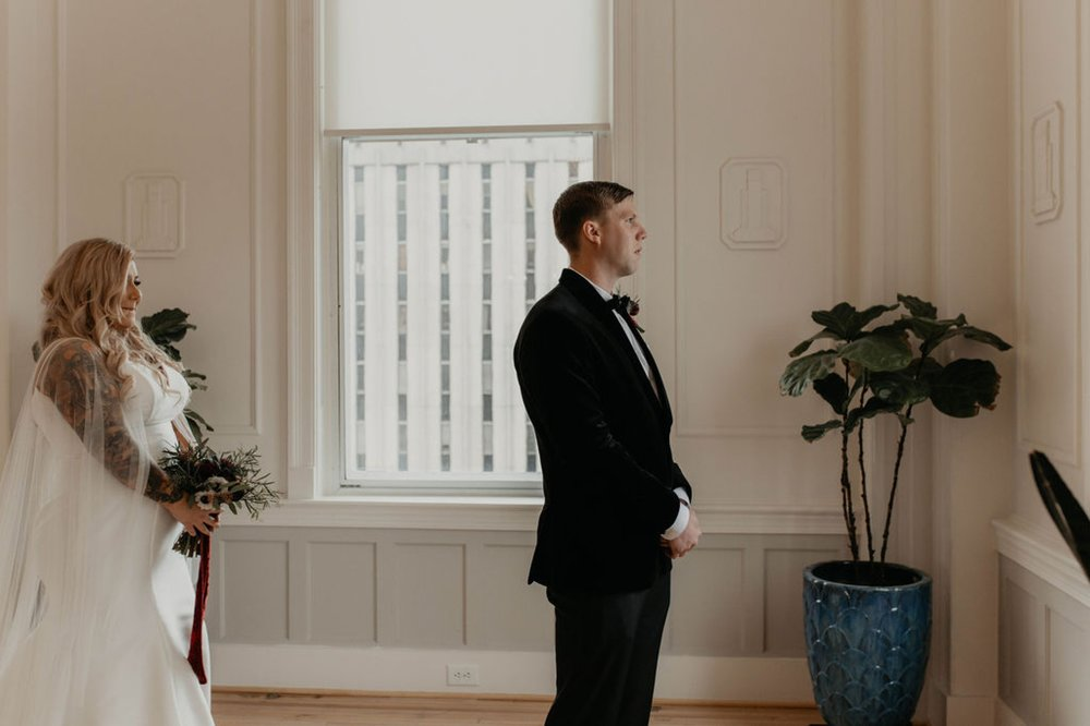 First look between bride and groom at the cannon room - Bride in an Allure Bridals Mermaid Gown - Matt Smarsh and Johanna Dye - suites by the black tux - Raleigh North Carolina Urban Edgy Downtown Wedding - suits by the black tux