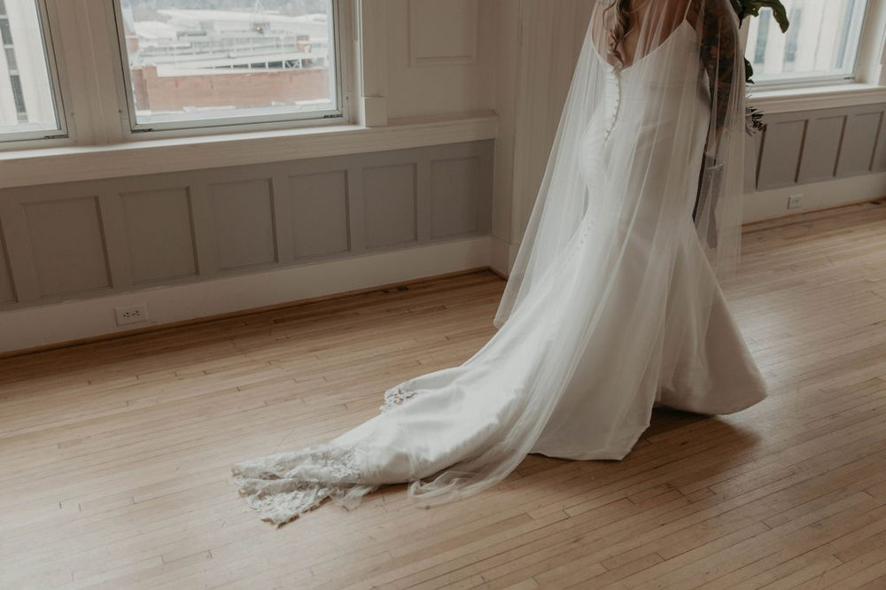 The cannon room - Bride walking  in an Allure Bridals Mermaid Gown - Matt Smarsh and Johanna Dye - suites by the black tux - Raleigh North Carolina Urban Edgy Downtown Wedding - suits by the black tux