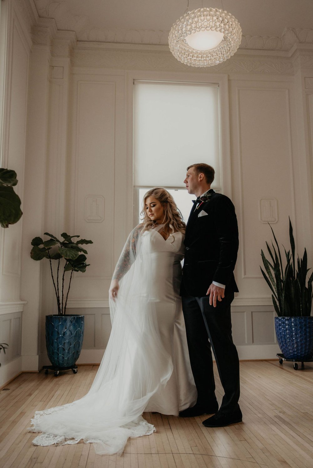 Bride and Groom at the Cannon Room looking out the window for a indoor portrait - Bride in an Allure Bridals Mermaid Gown - Matt Smarsh and Johanna Dye - suites by the black tux - Raleigh North Carolina Urban Edgy Downtown Wedding - suits by the black tux