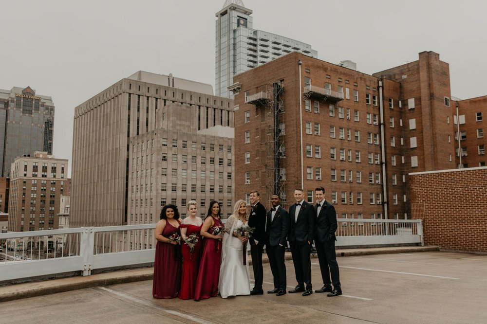 Downtown Wedding Party Portraits on top of a parking garage with the skyline in the background -  Bride in an Allure Bridals Mermaid Gown - Burgundy Bridesmaids dresses by davids bridal Matt Smarsh and Johanna Dye - suites by the black tux - Raleigh North Carolina Urban Edgy Downtown Wedding - suits by the black tux