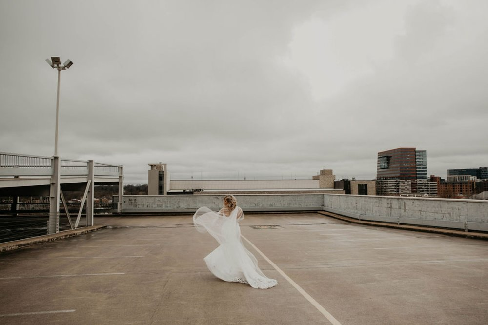 Downtown Bride portraits on top of a parking garage with the skyline in the background - Bride has a noontothemoon cape - Bride in an Allure Bridals Mermaid Gown - Burgundy Bridesmaids dresses by davids bridal Matt Smarsh and Johanna Dye - suites by the black tux - Raleigh North Carolina Urban Edgy Downtown Wedding - suits by the black tux