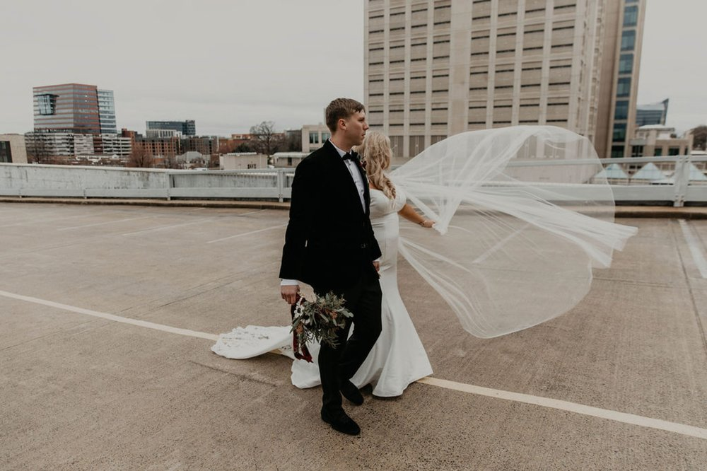 Downtown Bride and Groom portraits on top of a parking garage with the skyline in the background - Bride in an Allure Bridals Mermaid Gown - Burgundy Bridesmaids dresses by davids bridal Matt Smarsh and Johanna Dye - suites by the black tux - Raleigh North Carolina Urban Edgy Downtown Wedding - suits by the black tux