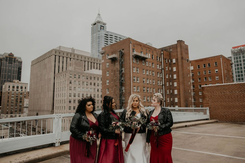 Edgy Bridesmaids portraits with Leather Jackets downtown with the skyline in the background - Bride in an Allure Bridals Mermaid Gown - Burgundy Bridesmaids dresses by davids bridal Matt Smarsh and Johanna Dye - suites by the black tux - Raleigh North Carolina Urban Downtown Wedding - suits by the black tux