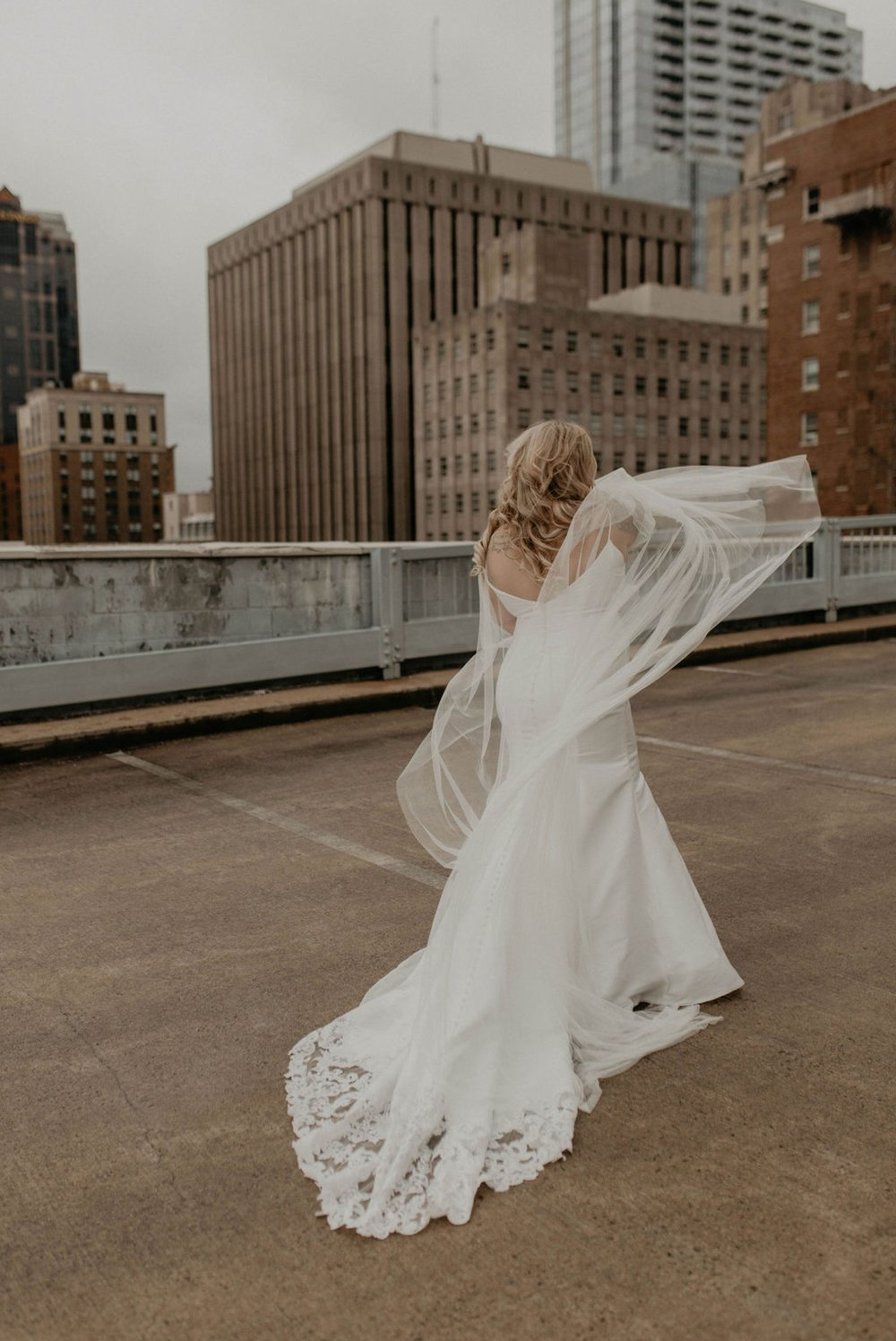 Downtown Bride portraits on top of a parking garage with the skyline in the background - Bride playing with her noontothemoon bridal cape - Bride in an Allure Bridals Mermaid Gown - Burgundy Bridesmaids dresses by davids bridal Matt Smarsh and Johanna Dye - suites by the black tux - Raleigh North Carolina Urban Edgy Downtown Wedding - suits by the black tux