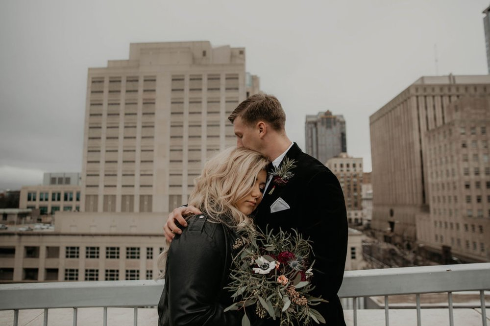 Wedding Portraits - Groom hugging bride - Bride in an Allure Bridals Mermaid Gown and a leather jacket - Burgundy Bridesmaids dresses by davids bridal Matt Smarsh and Johanna Dye - suites by the black tux - Raleigh North Carolina Urban Downtown Wedding - suits by the black tux