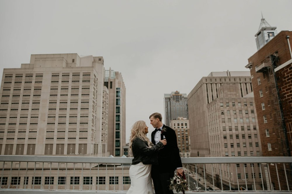 Wedding Portraits in front of the raleigh skyline  - - Bride in an Allure Bridals Mermaid Gown and a leather jacket - Burgundy Bridesmaids dresses by davids bridal Matt Smarsh and Johanna Dye - suites by the black tux - Raleigh North Carolina Urban Downtown Wedding - suits by the black tux