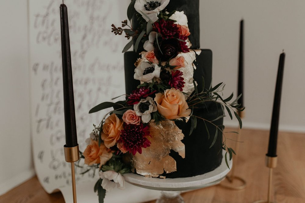 Black wedding cake with gold and flower accents by sugar euphoria at the Glassbox at 230 - til death cake topper - Matt Smarsh and Johanna Dye - suites by the black tux - Raleigh North Carolina Urban Downtown Wedding