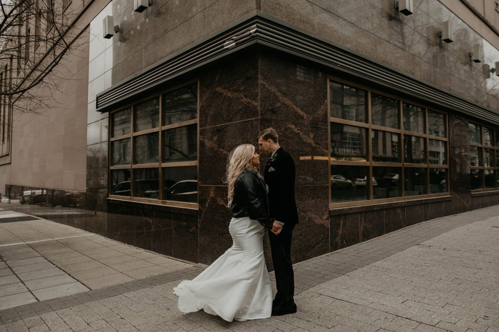 bride and groom looking at each other in downtown raleigh - Bride in an Allure Bridals Mermaid Gown and a leather jacket - Burgundy Bridesmaids dresses by davids bridal Matt Smarsh and Johanna Dye - suites by the black tux - Raleigh North Carolina Urban Downtown Wedding - suits by the black tux