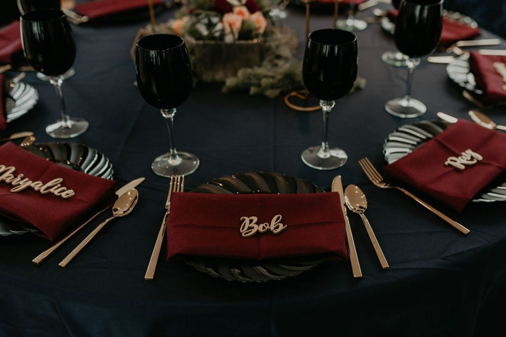 dark wedding table decorations - Navy tablecloth with burgundy napkins and gold laser cut name place cards, gold silverwear and black plates and black wine glasses by ce rental - Bride in an Allure Bridals Mermaid Gown and a leather jacket - Burgundy Bridesmaids dresses by davids bridal Matt Smarsh and Johanna Dye - Raleigh North Carolina Urban Downtown Wedding