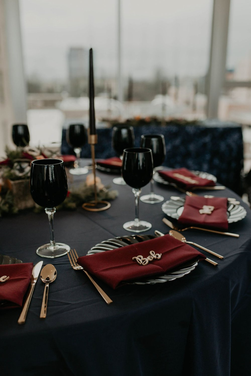 dark wedding table decorations - Navy tablecloth with burgundy napkins and gold laser cut name place cards, gold silverwear and black plates and black wine glasses by ce rental - gold candle stick holder with black candles - Matt Smarsh and Johanna Dye - Raleigh North Carolina Urban Downtown Wedding