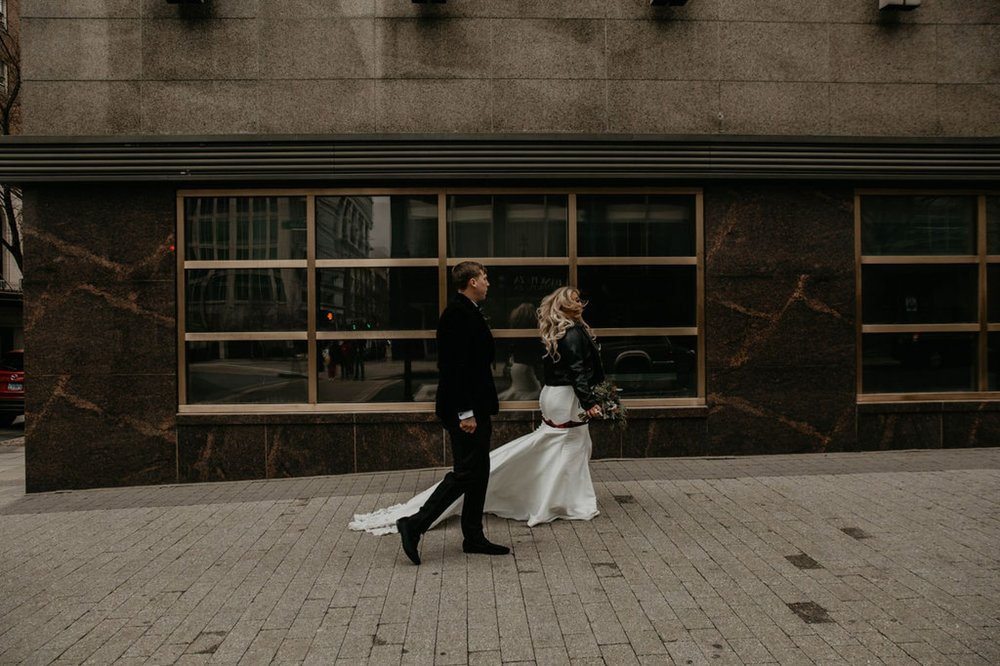 bride and groom walking downtown - Bride in an Allure Bridals Mermaid Gown and a leather jacket - Burgundy Bridesmaids dresses by davids bridal Matt Smarsh and Johanna Dye - suites by the black tux - Raleigh North Carolina Urban Downtown Wedding - suits by the black tux