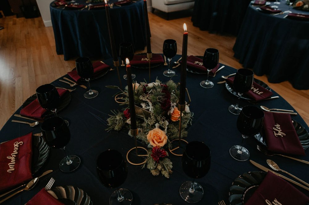 sweetheart table - dark wedding table decorations - Navy tablecloth with burgundy napkins and gold laser cut name place cards, gold silverwear and black plates and black wine glasses by ce rental - dark flowers centerpiece - gold table number - gold candle stick holder with black candles - Matt Smarsh and Johanna Dye - Raleigh North Carolina Urban Downtown Wedding at the Glass Box at 230