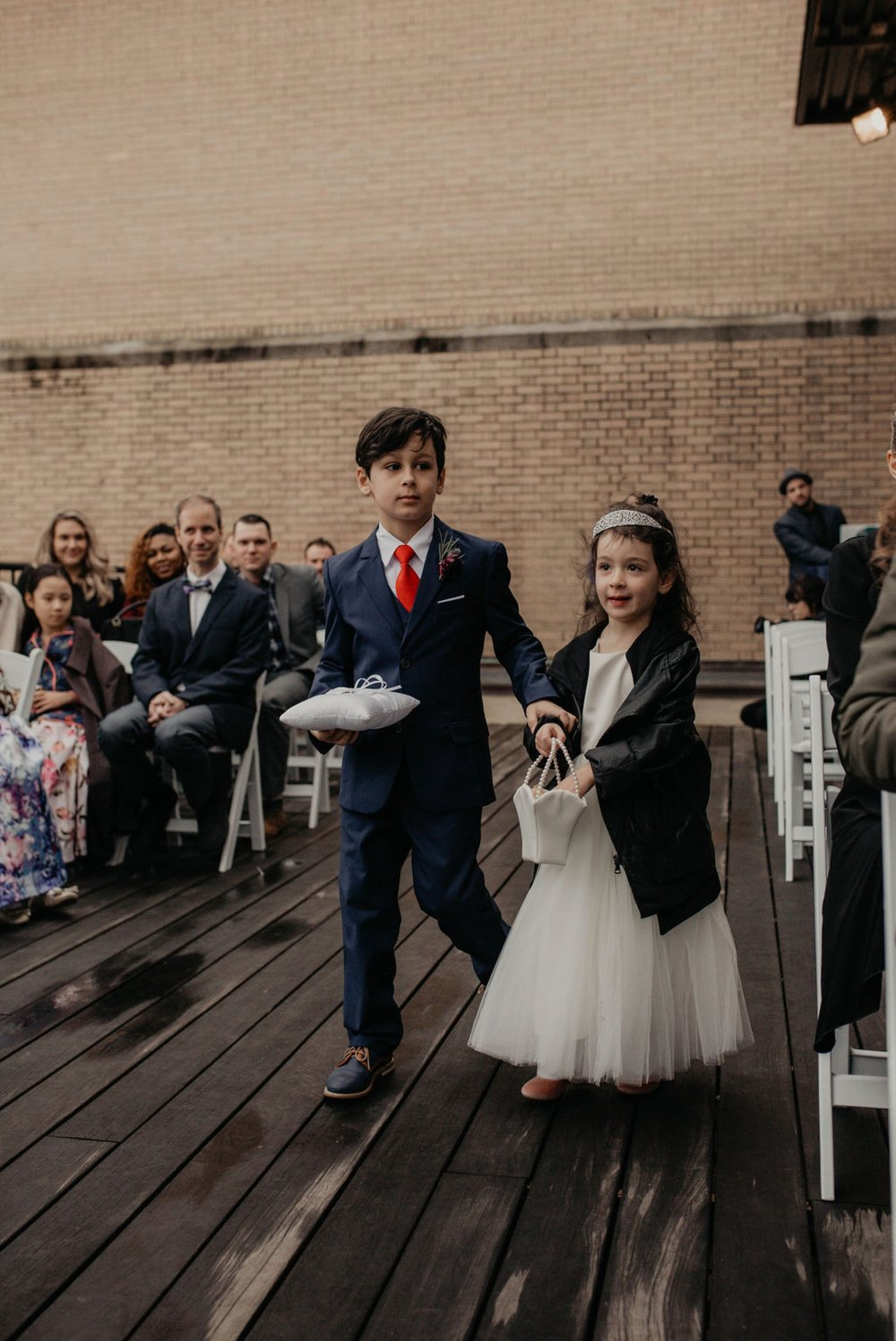 Ring BEarer and flower girl in leather jacket walking down the aisle - Wedding Ceremony Details on a rooftop terrace with the skyline in the background - Matt Smarsh and Johanna Dye - Raleigh North Carolina Urban Downtown Wedding at the Glass Box at 230