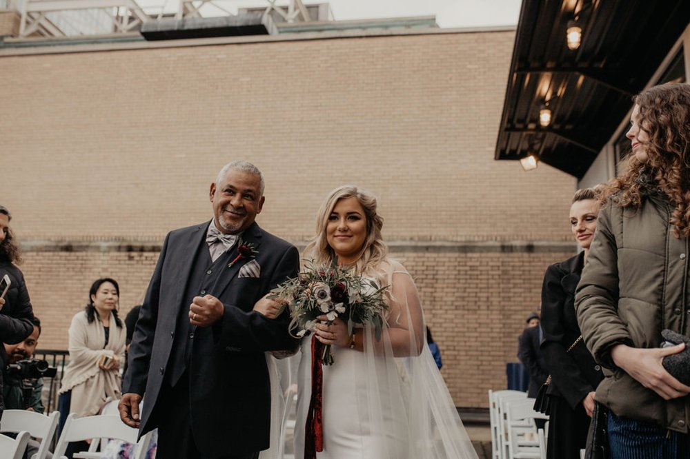 Father and Bride walking down the aisle - Wedding Ceremony on a rooftop terrace with the skyline in the background - Matt Smarsh and Johanna Dye - Raleigh North Carolina Urban Downtown Wedding at the Glass Box at 230