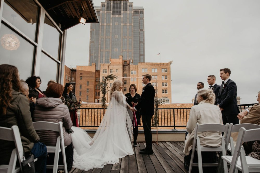 Bride and Groom holding hands - Wedding Ceremony on a rooftop terrace with the skyline in the background - Matt Smarsh and Johanna Dye - Raleigh North Carolina Urban Downtown Wedding at the Glass Box at 230