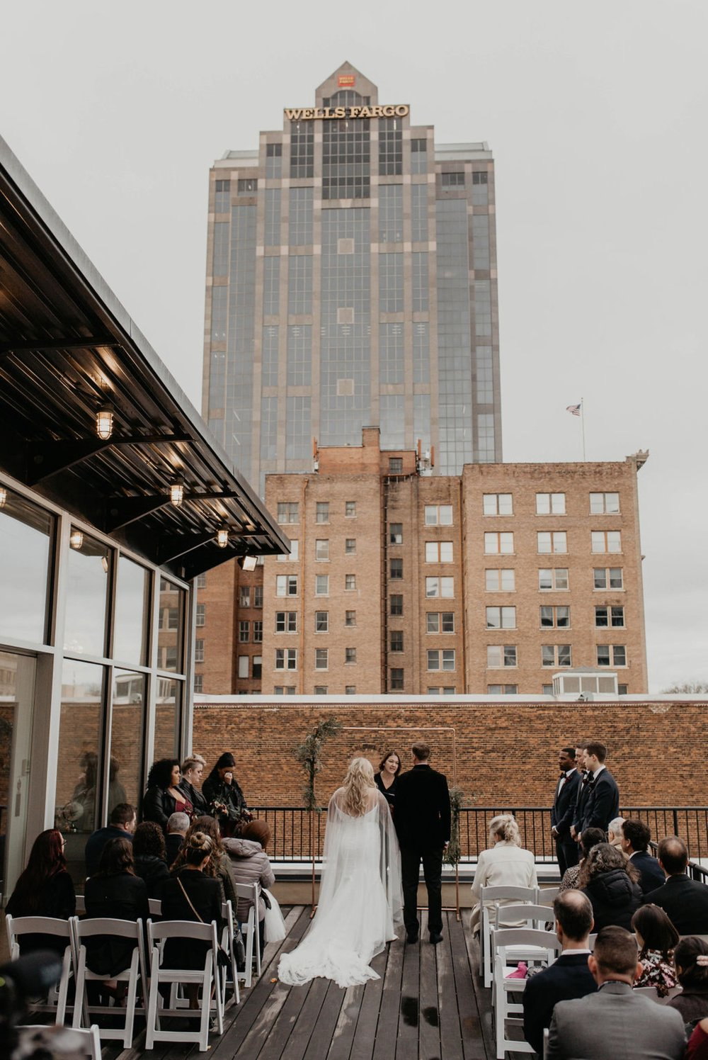 Wedding Ceremony on a rooftop terrace with the skyline in the background - Matt Smarsh and Johanna Dye - Raleigh North Carolina Urban Downtown Wedding at the Glass Box at 230