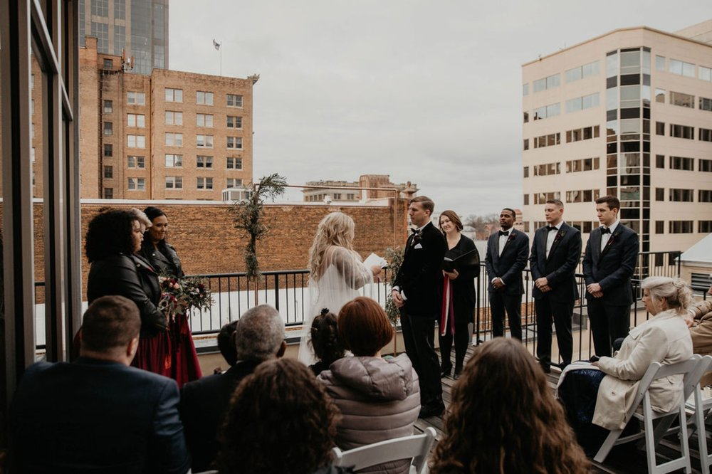 Bride reading her vows - Wedding Ceremony on a rooftop terrace with the skyline in the background - Matt Smarsh and Johanna Dye - Raleigh North Carolina Urban Downtown Wedding at the Glass Box at 230