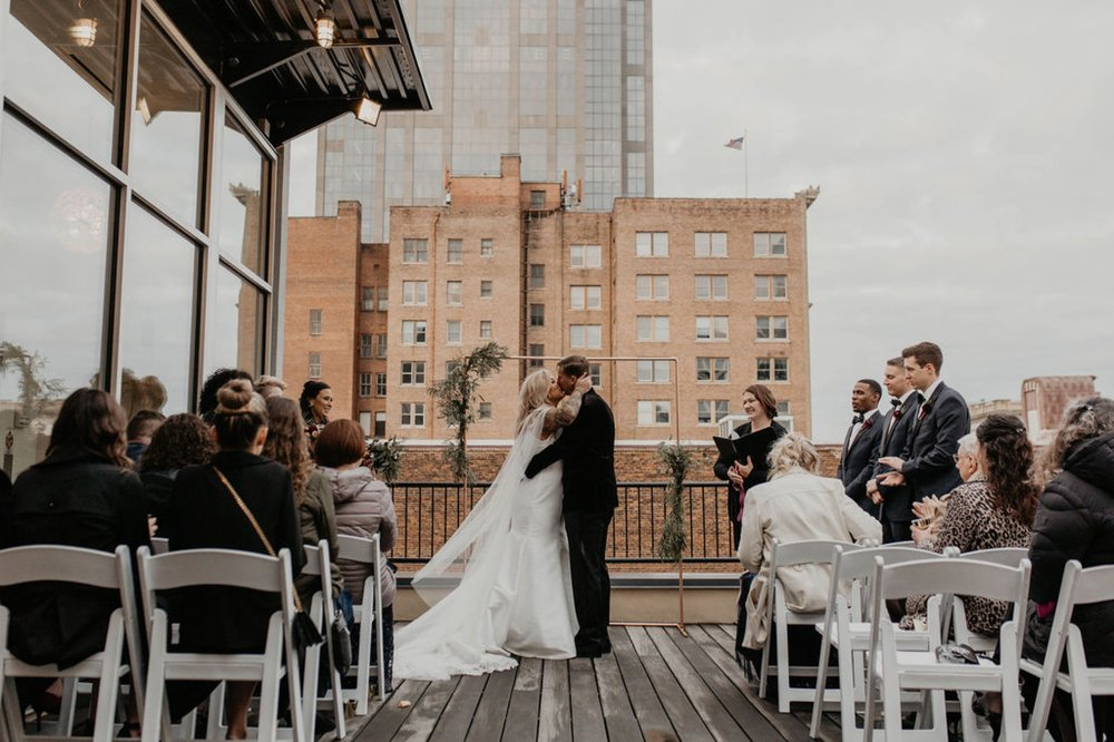 First kiss between bride and groom - Wedding Ceremony on a rooftop terrace with the skyline in the background - Matt Smarsh and Johanna Dye - Raleigh North Carolina Urban Downtown Wedding at the Glass Box at 230