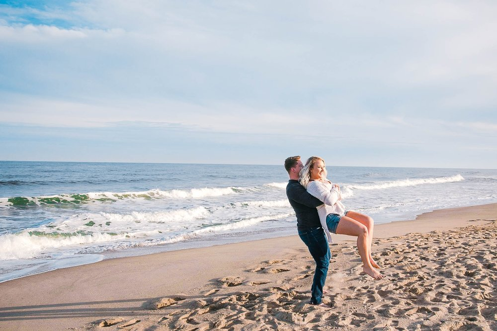fiance being playful on the beach - girl wearing ripped jeans shorts and a white free people sweater - Casual Beach Engagement Photography Session - Honolulu Oahu Hawaii Wedding Photographer - Johanna Dye