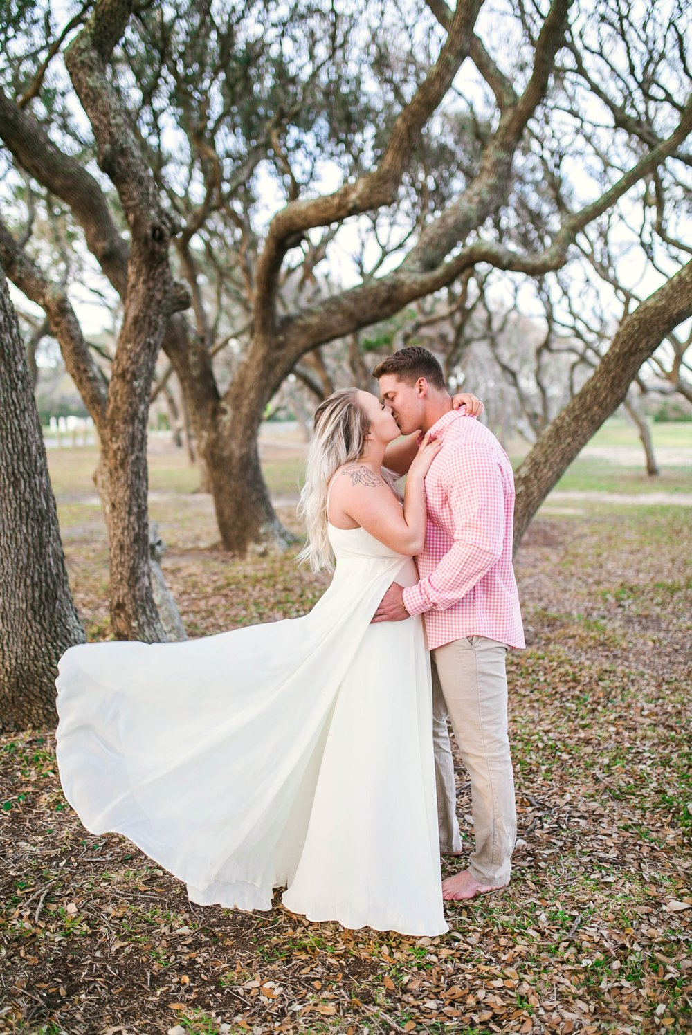 Engagement Photography Session beneath tropical trees - man kissing his fiance - girl is wearing a white flowy maxi dress from lulus - Honolulu Oahu Hawaii Wedding Photographer - Johanna Dye