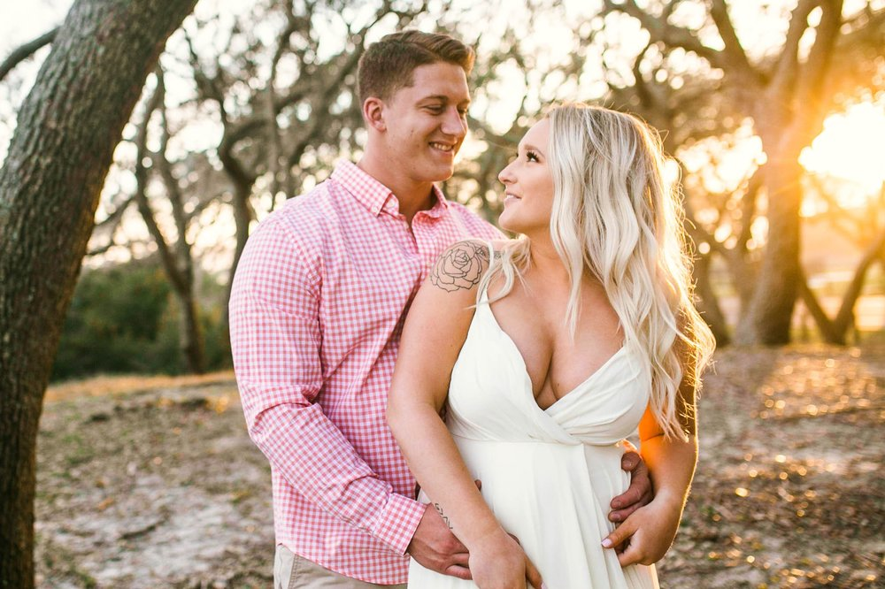 Engagement Photography Session beneath tropical trees at sunset during golden hour light - couple is looking at each other  - girl is wearing a white flowy maxi dress from lulus - Honolulu Oahu Hawaii Wedding Photographer - Johanna Dye