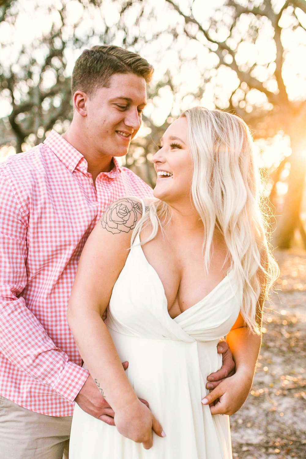 Engagement Photography Session beneath tropical trees at sunset during golden hour light - couple is laughing at each other - girl is wearing a white flowy maxi dress from lulus - Honolulu Oahu Hawaii Wedding Photographer - Johanna Dye