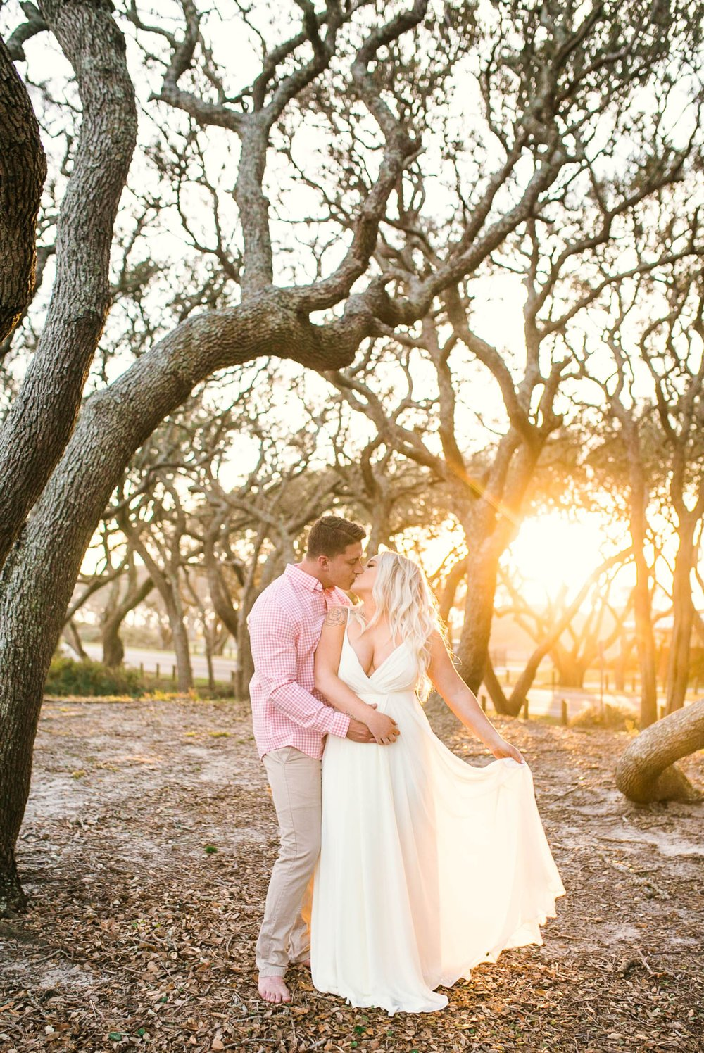 Engagement Photography Session beneath tropical trees at sunset during golden hour light - man kissing his fiance, woman is playing with her dress - girl is wearing a white flowy maxi dress from lulus - Honolulu Oahu Hawaii Wedding Photographer - Johanna Dye