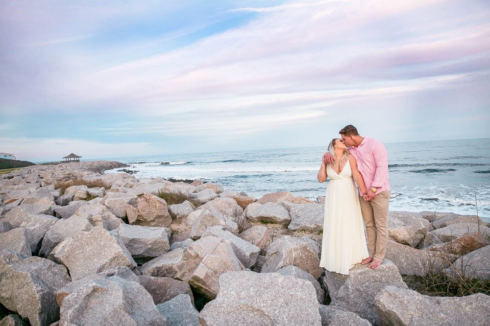 Engagement Photography Session at the beach on top of rocks with a cotton candy sky in the background - couple is hugging each other- girl is wearing a white flowy maxi dress from lulus - Honolulu Oahu Hawaii Wedding Photographer - Johanna Dye