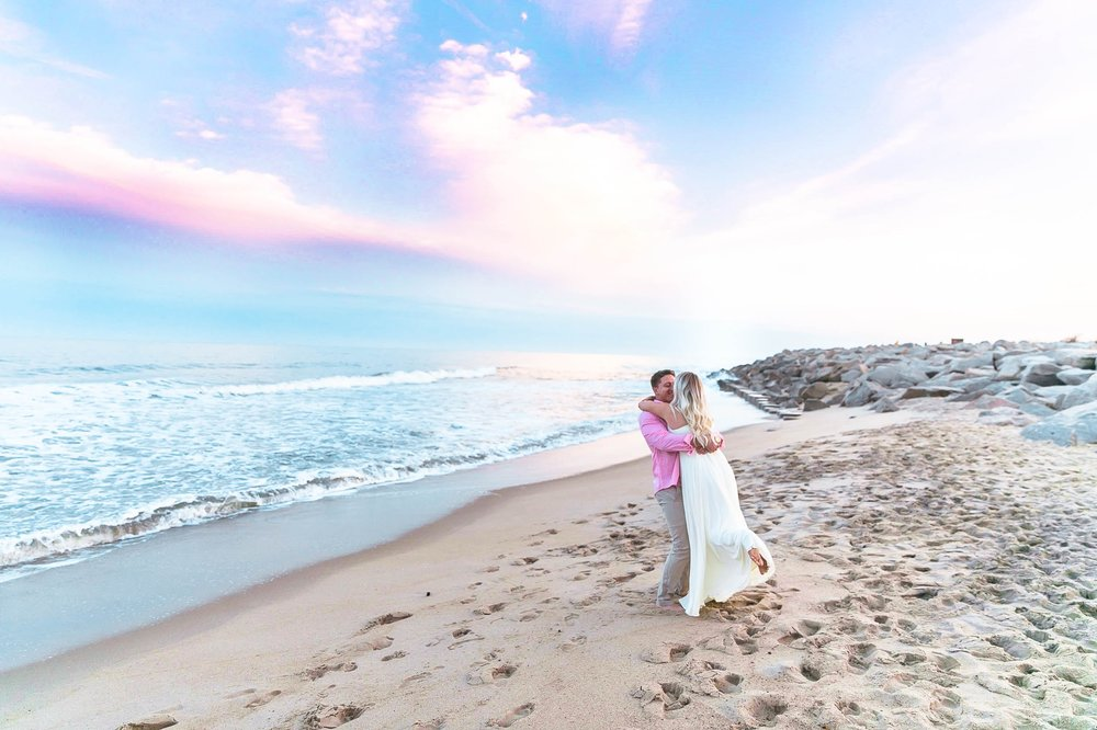 Romantic Engagement Photography Session at the beach during sunset with a cotton candy sky - guy is picking up his fiance for a kiss and swinging her around - girl is wearing a white flowy maxi dress from lulus - Honolulu Oahu Hawaii Wedding Photographer - Johanna Dye