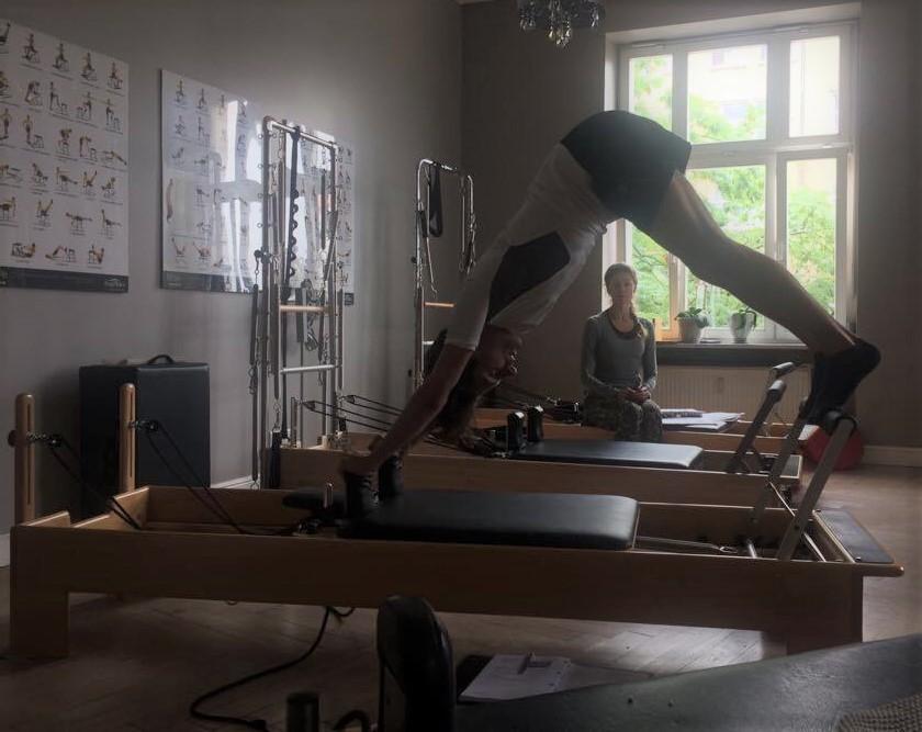 Übung auf dem Reformer, ein klassisches Pilatesgerät mit Widerstand aus Springfedern.
