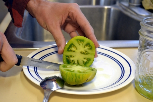 Cut the tomatoes in half width-wise to expose the seeds.