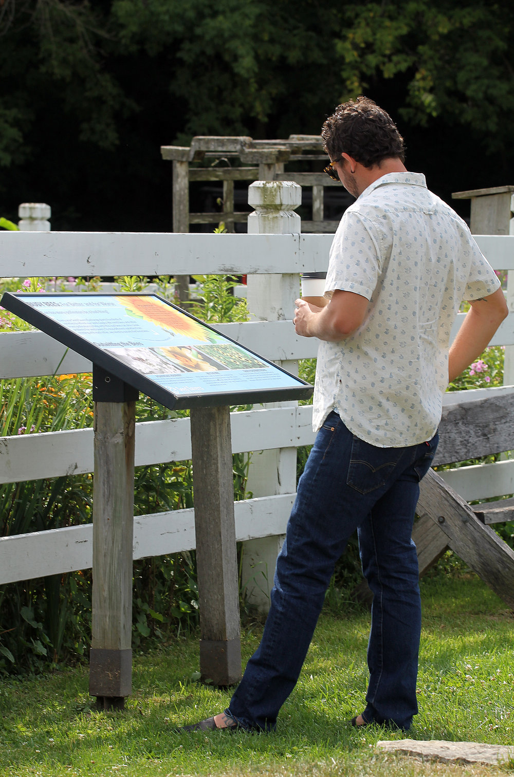 A visitor reads about pollination outside Diane's Garden.