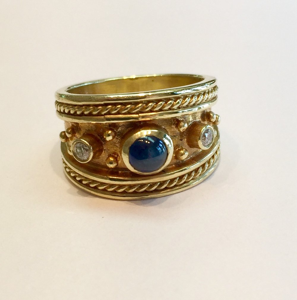 Item No. A104 USD775  14k Yellow Gold Sapphire and Diamond Ring.  If you like Etruscan style jewelry, you will love this ring.A .65 carat sapphire with two 8 point diamonds either side along with 10.3 grams of 14k gold makes this a classic and a substantial piece.