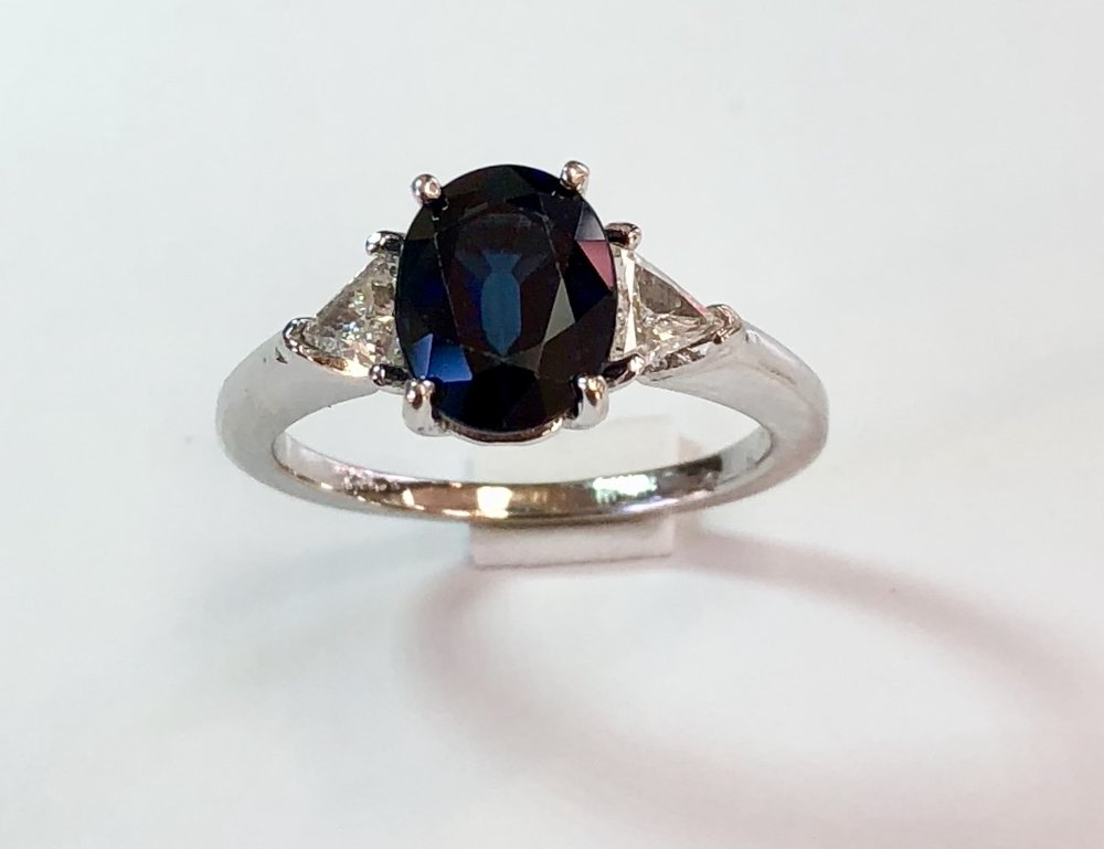 Item no. 348 US$1,445  Stamped 18k White Gold and Blue Sapphire Diamond Ring.  Stunning dark blue centre sapphire weighting 2.69 carats, flanked by two high end trillion cut diamonds weighing .8 carat in total.  A classic ring that is made with very high quality gold and gemstones.  4.1 grams