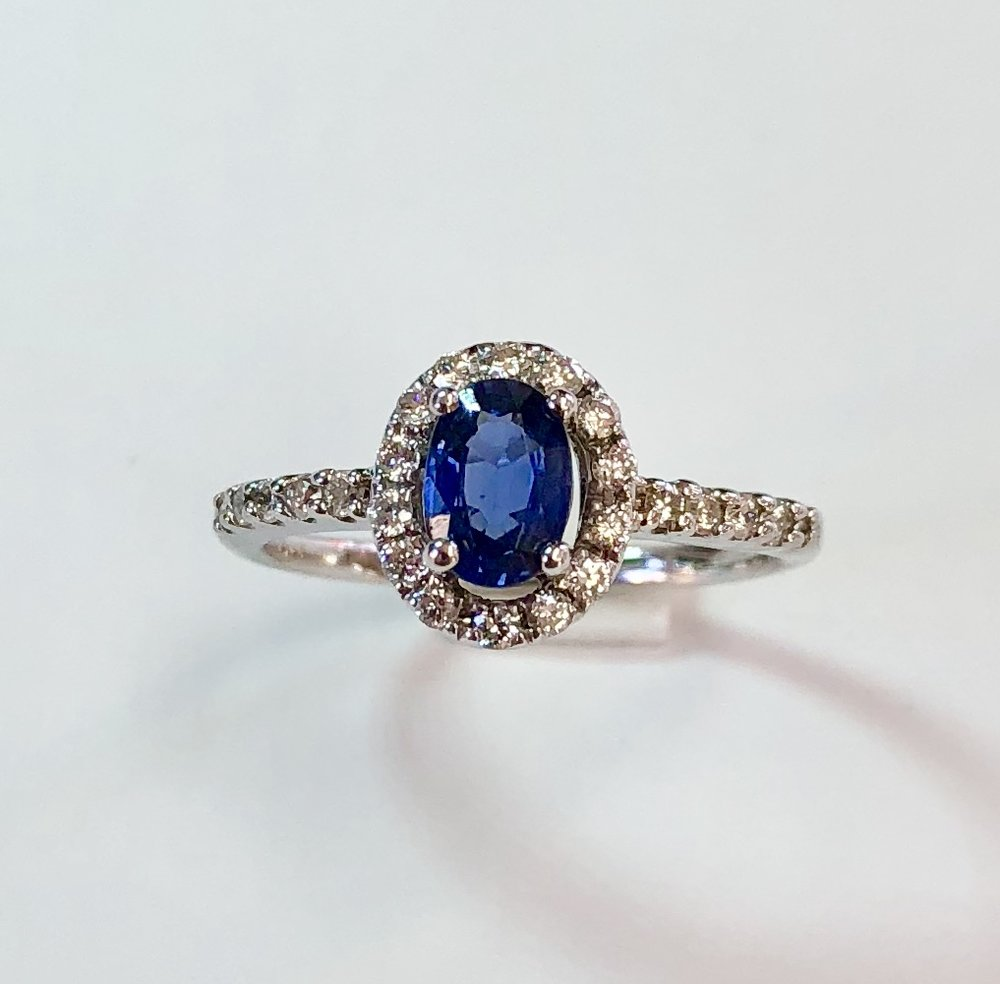 Item no.265 US$475  14k White Gold Sapphire and Diamond Ring.  Beautiful blue sapphire of approximately .75 carats with a halo of lovely white high quality diamonds. Diamonds are also down the sides of the ring and weight a total of approximately .36 carats in total.  Understated and fabulous quality.  1.9 grams