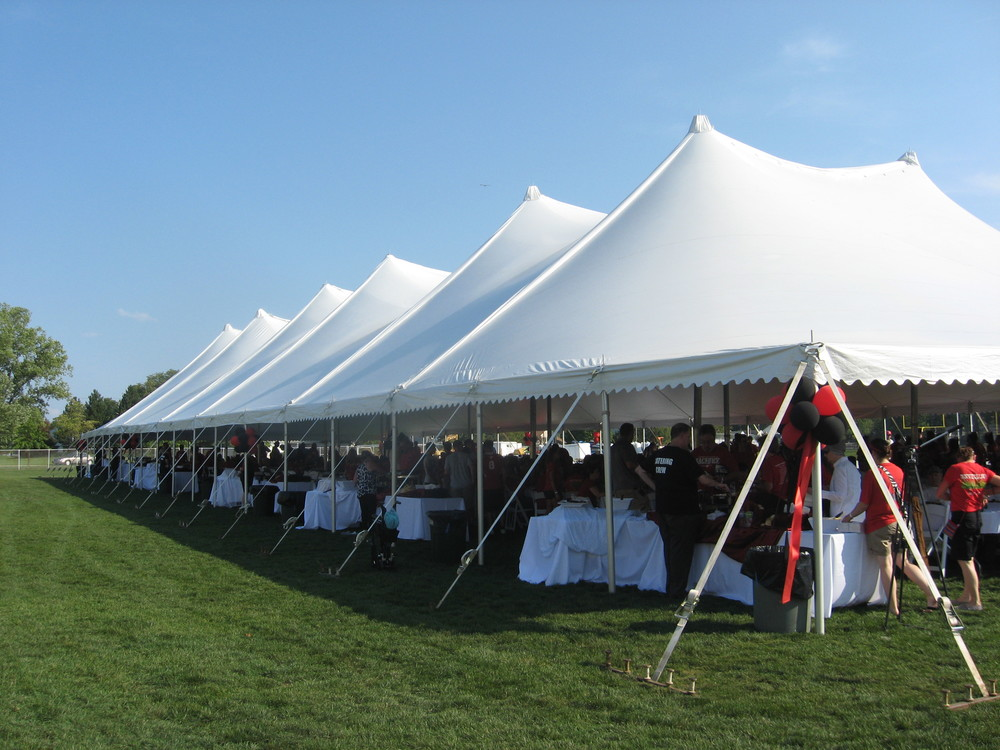 A pole tent covering a gathering of 1,000 guests.