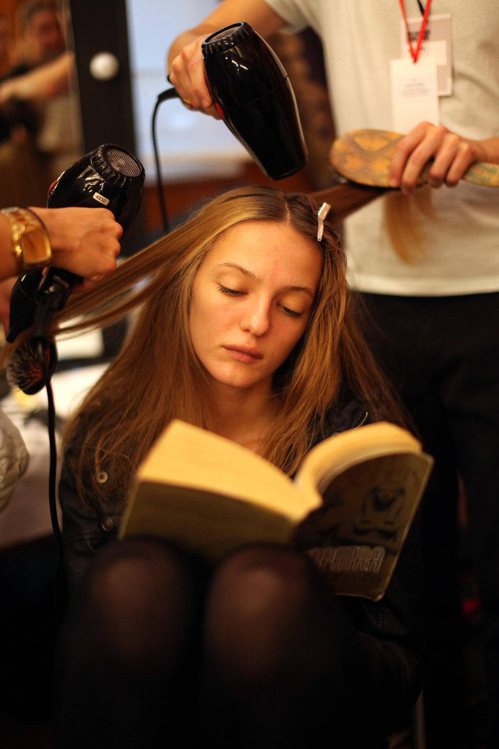 A model backstage at London Fashion Week squeezes in some reading time before a catwalk show.  Pic: Katie Collins/PA images