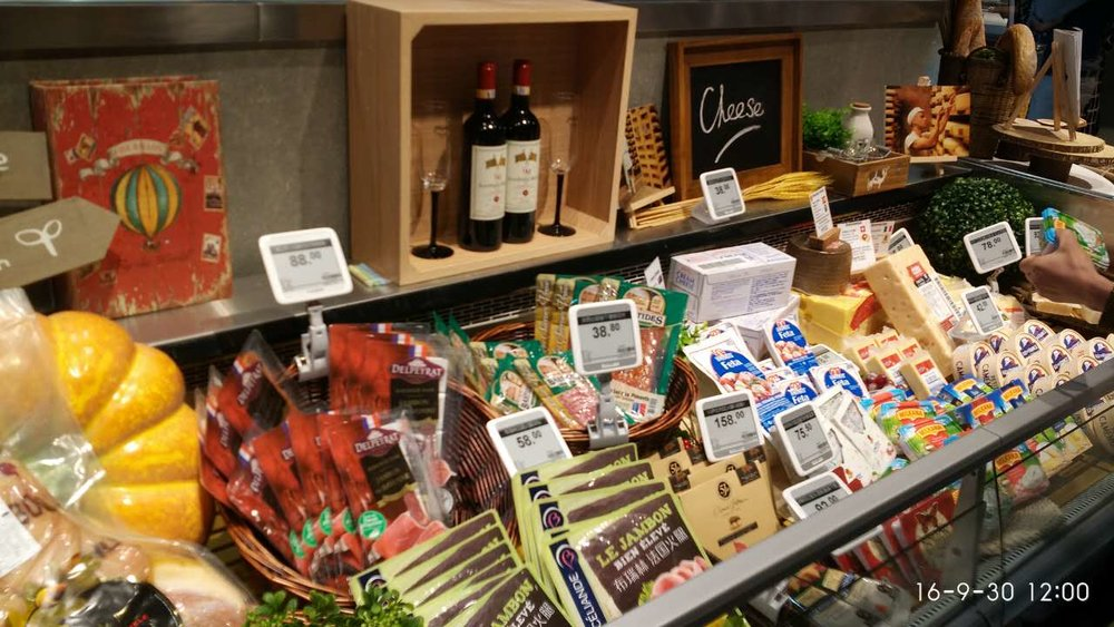 Electronic shelf labels are fixed via clamps and stands to a refrigerated cheese display.