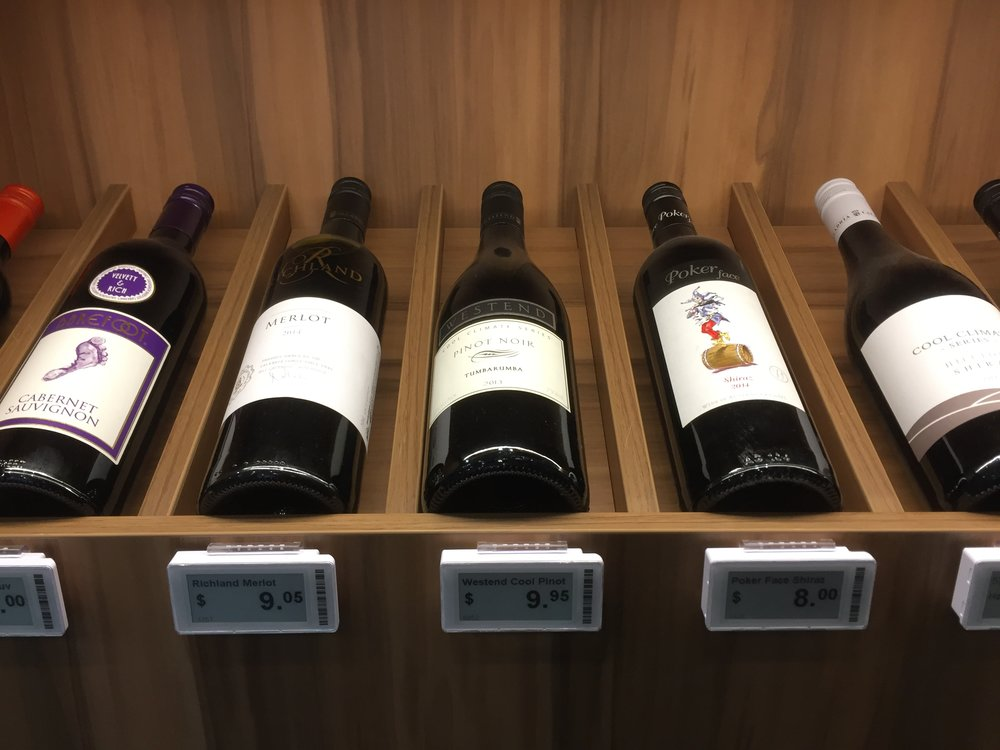 Sydney bottle shop red wine display with ESLs