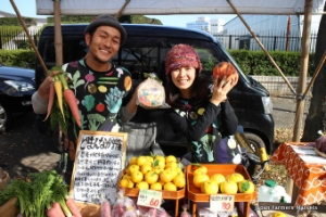 Two Japanese farmers selling their produce (including yuzu) at a farmer's market.