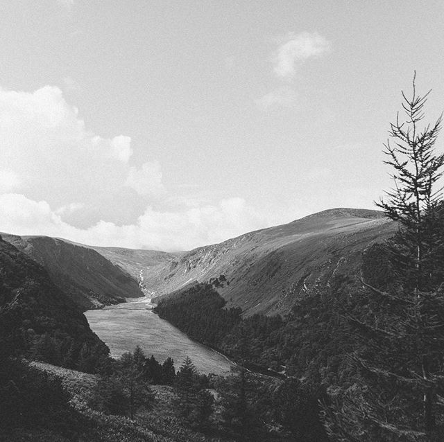 Glendalough, Wicklow Mountains National Park, Ireland, 2017. The view from the car park at the foot of this valley was one of ill-prepared walkers absolutely sodden from flash rain showers, all making a dash for their vehicles. We'd been sat in the dry of ours for a while, just monitoring the skies and eventually decided to brave it. We did the long walk (there were many options) and was gifted many views like this one. As soon as we arrived back to our car the skies opened up once again. Timed that one just right.  #suzyandalex #suzywimbournephotography #liveforthestory #wanderlust #adventurealways #livefolk #lifeofadventure #glendalough #wicklowmountains #blackandwhitephotography