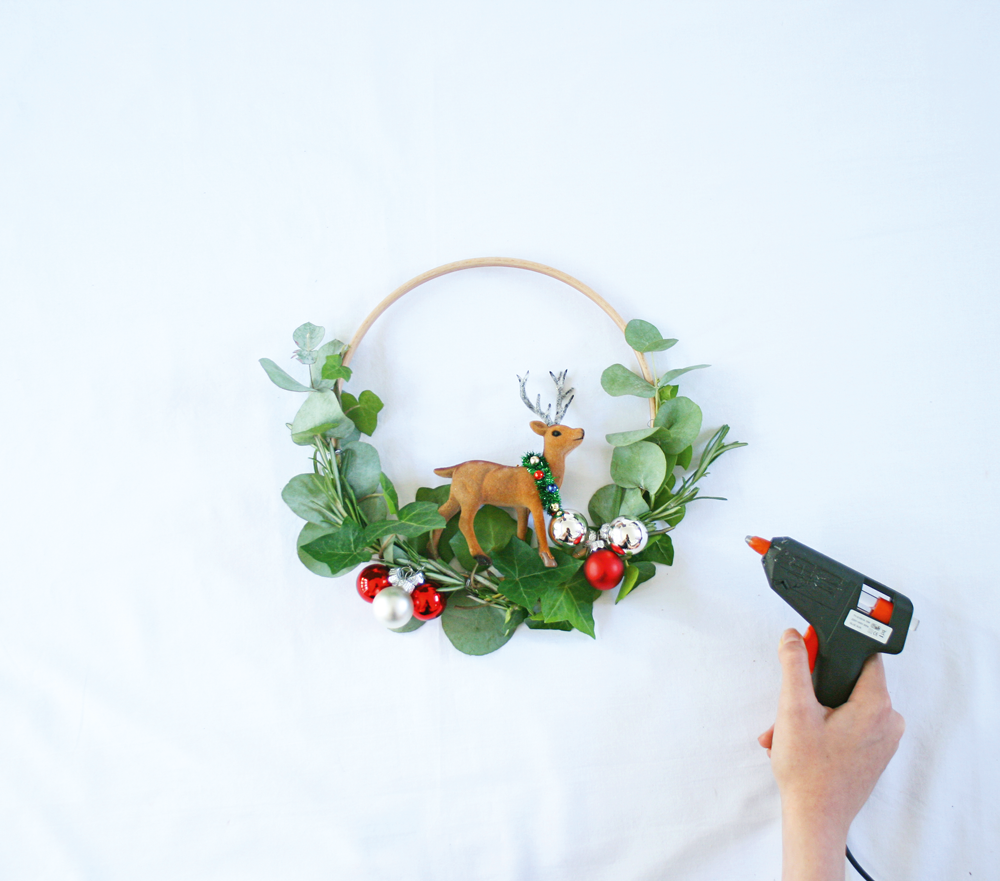 3 Remove any hanging loops from your tree decoration, then glue it securely to the centre of the hoop base using a glue gun. Leave the whole hoop piece aside to dry.