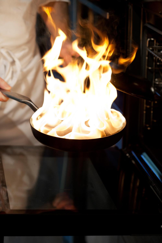 4.    Ha et lokk i den ene hånden når du løfter pannen over til den åpne stekeovnen, hvor fisken ligger på rist øverst og isbitene på stekebrettet på midten.