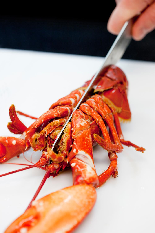 4. Hvis hummeren skal spises naturell bør den kokes dagen før, og oppbevares kaldt til du skal bruke den, slik at smaken får satt seg til den deles i to. Del den med en sagtakket kniv, og pass på at du skjærer rent gjennom den bøyde halen.