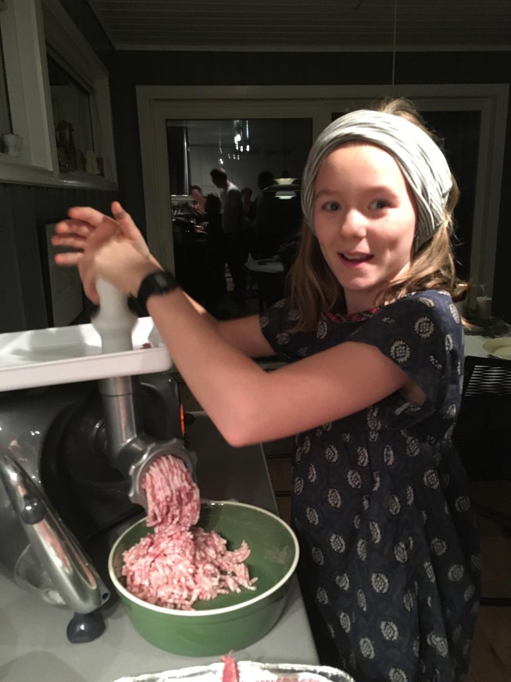 Ellinor (10) har vært på pølsekurs, og pisker oss andre til arbeid. Her kverner hun svinekjøtt og -spekk før det skal blandes ut med løk, hvitløk, chili, krydder og urter.